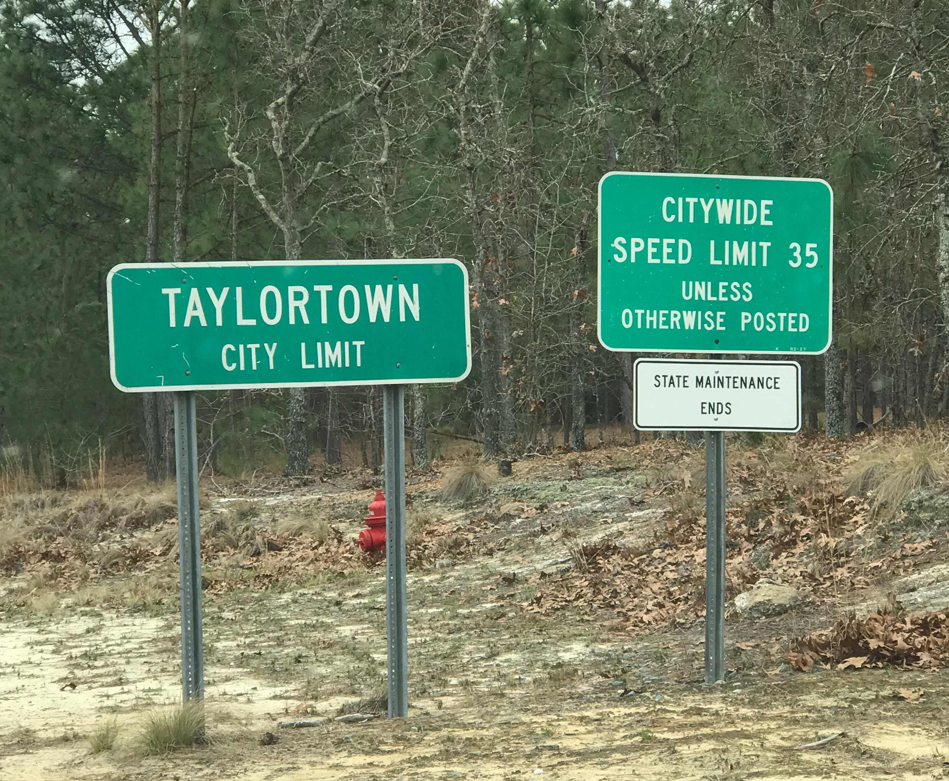 "Two signs are shown along the side of the highway. One reads ""Taylortown, City Limit"" and the other reads ""Citywide Speed Limit 35; Unless Otherwise Posted; State Maintenance Ends"""