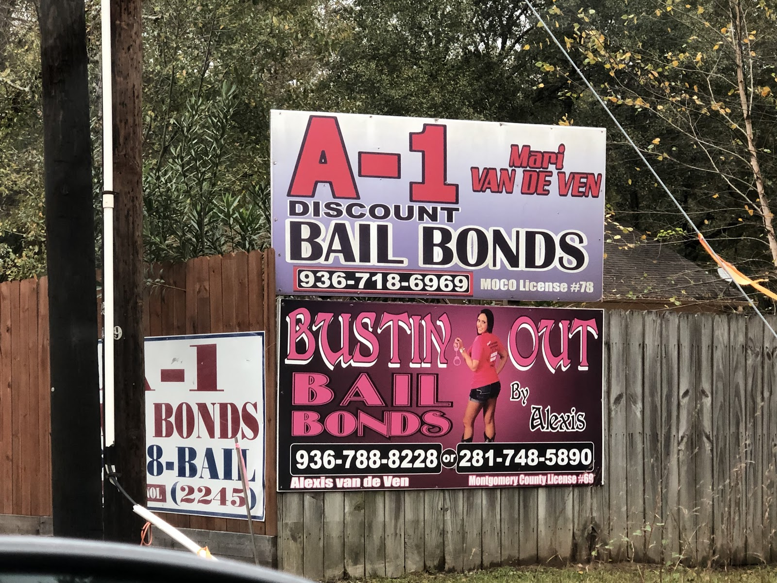 "Two pink and red road signs read ""A-1 Discount Bail Bonds"" and ""Bustin Out Bail Bonds"""