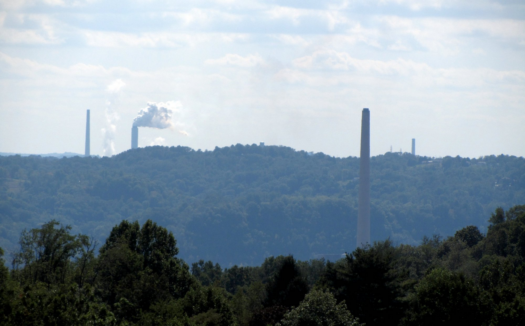 Smokestacks jutting out from the tree cover of the Ohio Valley