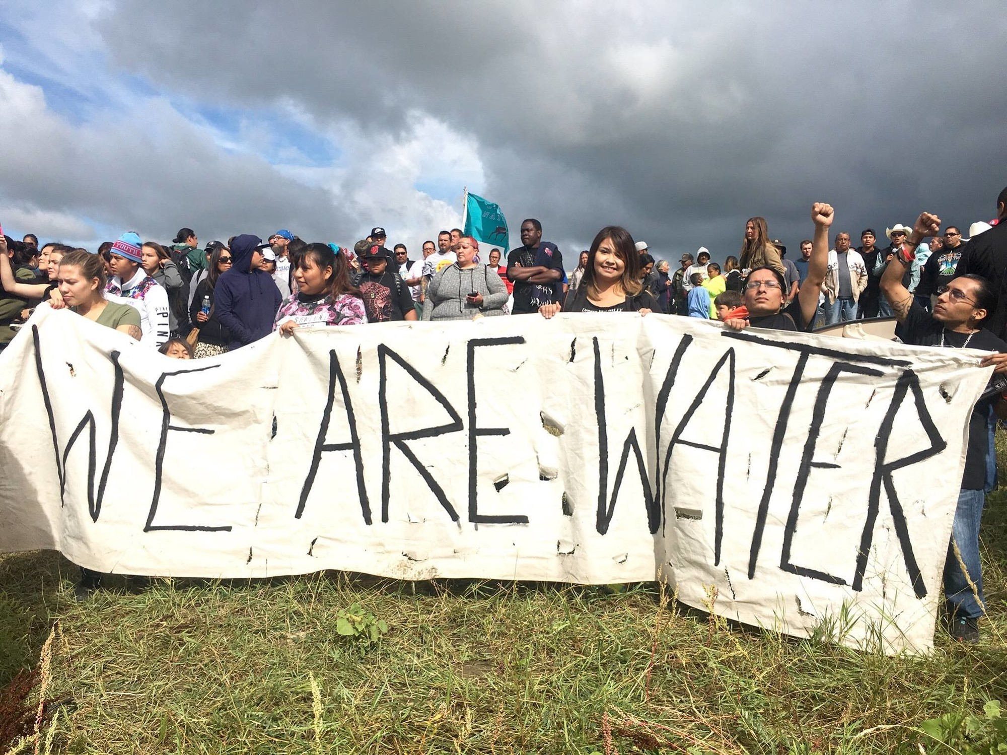 "A large group of Alaskans hold a ""WE ARE WATER"" banner as part of a Stand With Standing Rock #NoDAPL protest in 2016"
