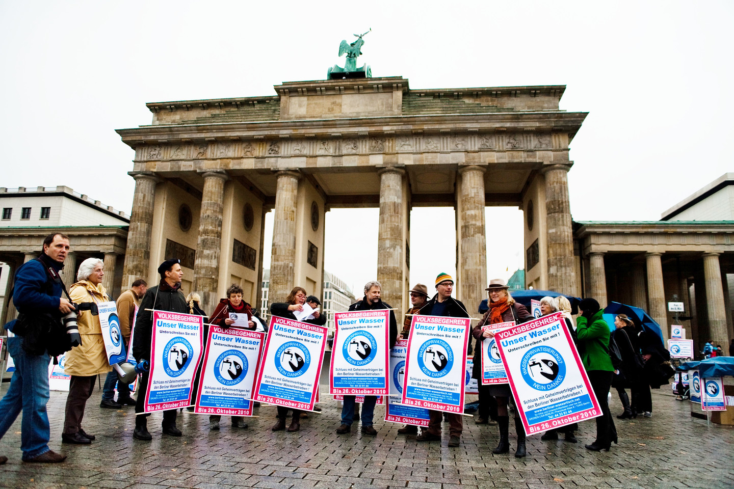 A group of water activists stand in front of the Brandenburger Tor holding protest signs.