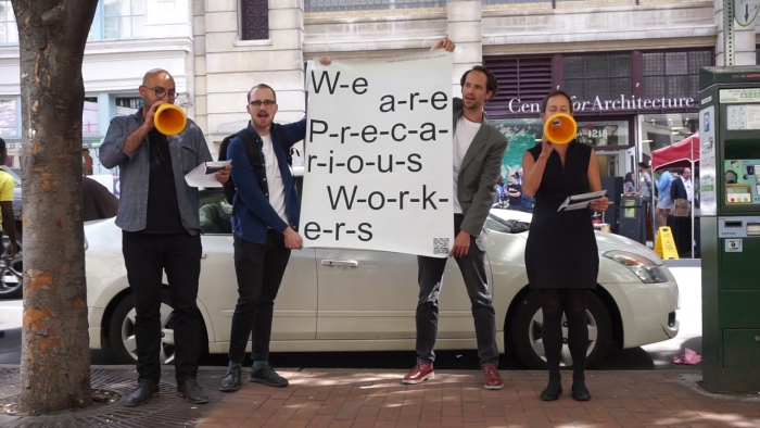 "Members of The Architecture Lobby performance, holding a sign that reads, ""We are Precarious Workers,"" outside the National AIA Convention in 2016"