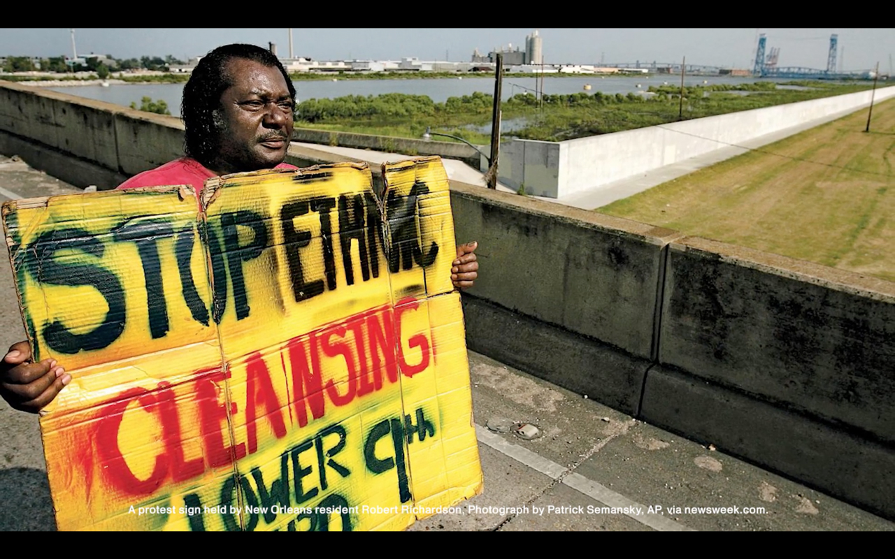 "An African-American person standing on an overpass holds a hand-written sign that reads ""Stop Ethnic Cleansing, Lower 9th Ward"""