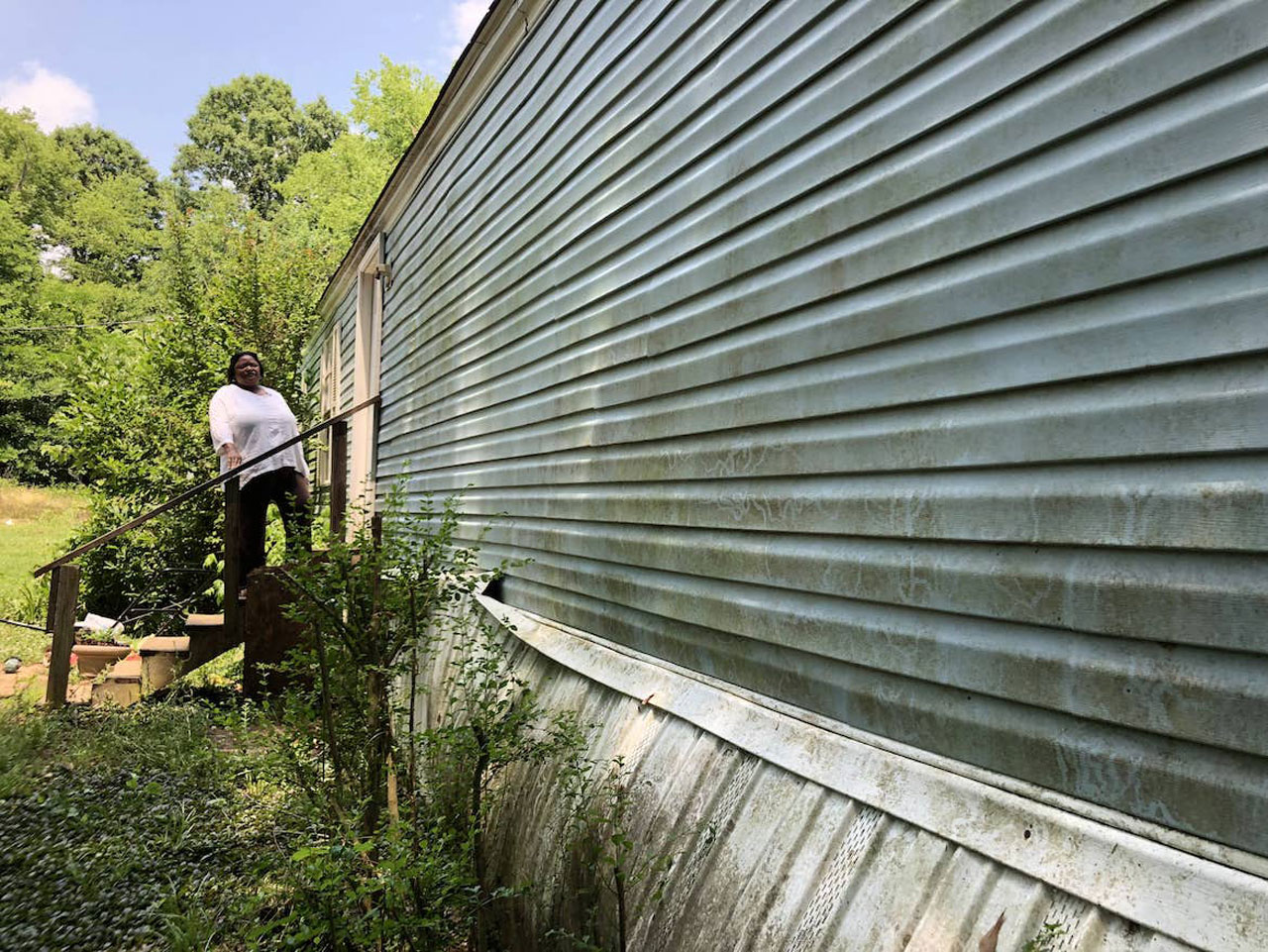 An African American woman stands on the steps to a mobile home, with shrubs in the foreground and trees in the background