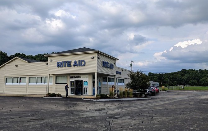 "A tan building with shuttered windows and ""Rite Aid"" in blue letters above an open door sits behind an empty parking lot."