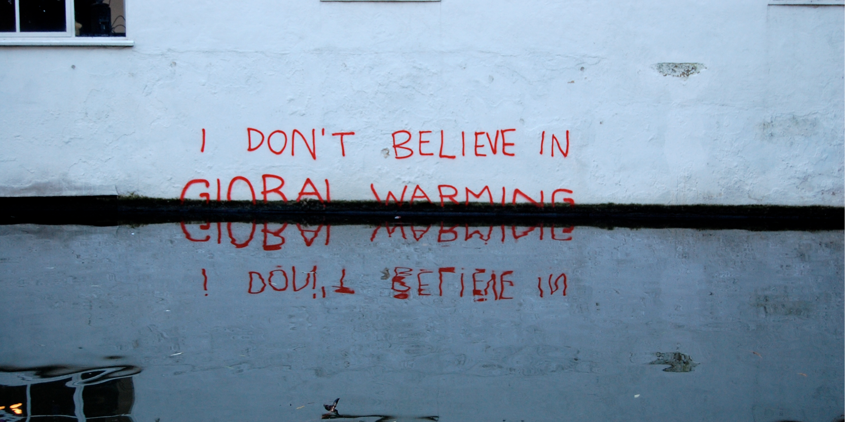 """I don't believe in Global Warming"" written in spray paint reflected in flooded groundwater"