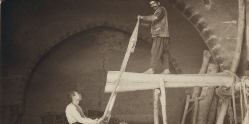 Archival photo from library of congress of two men sawing a log. One man stands on top of the log that is propped up, the other is on the ground. From Kamar ed Din Series: Hand-sawing of Logs into Planks, 1938.