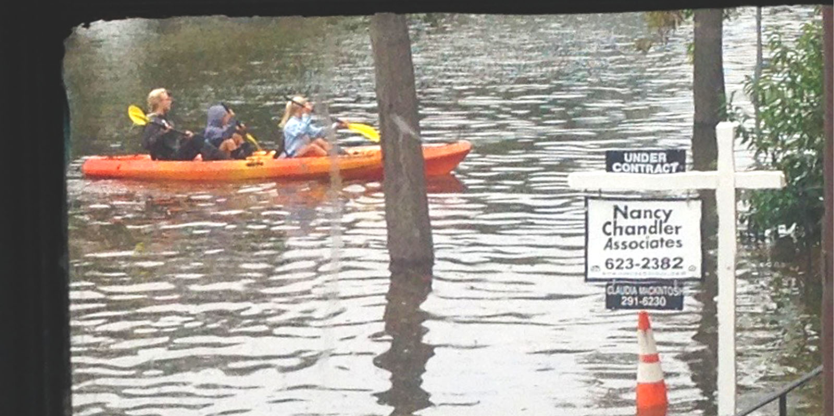 Three people on a kayak passing a for sale real estate sign in flooded area in southeastern Virginia.
