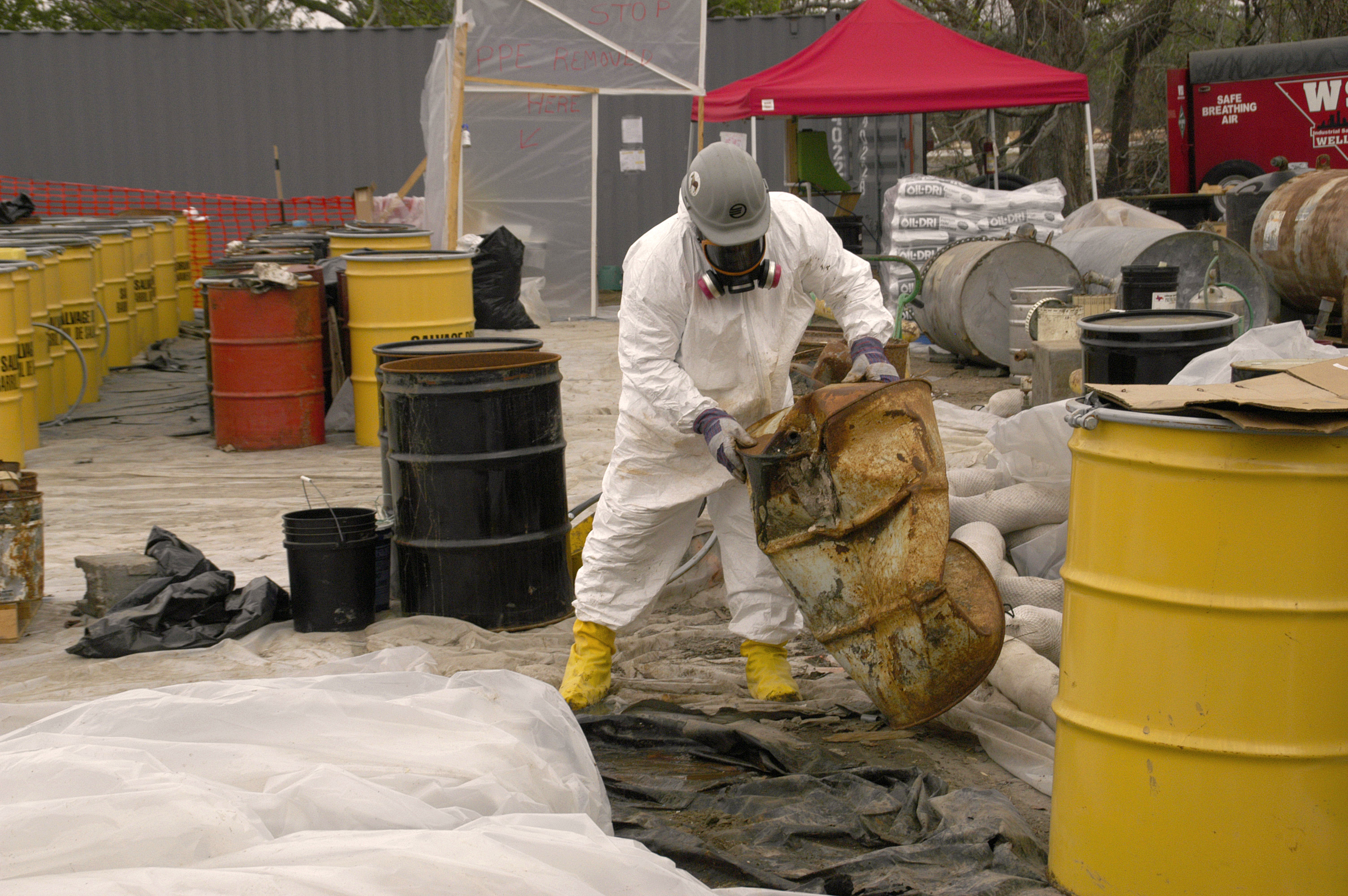 A worker in hazmat suit checks a potentially hazardous barrel to determine its contents