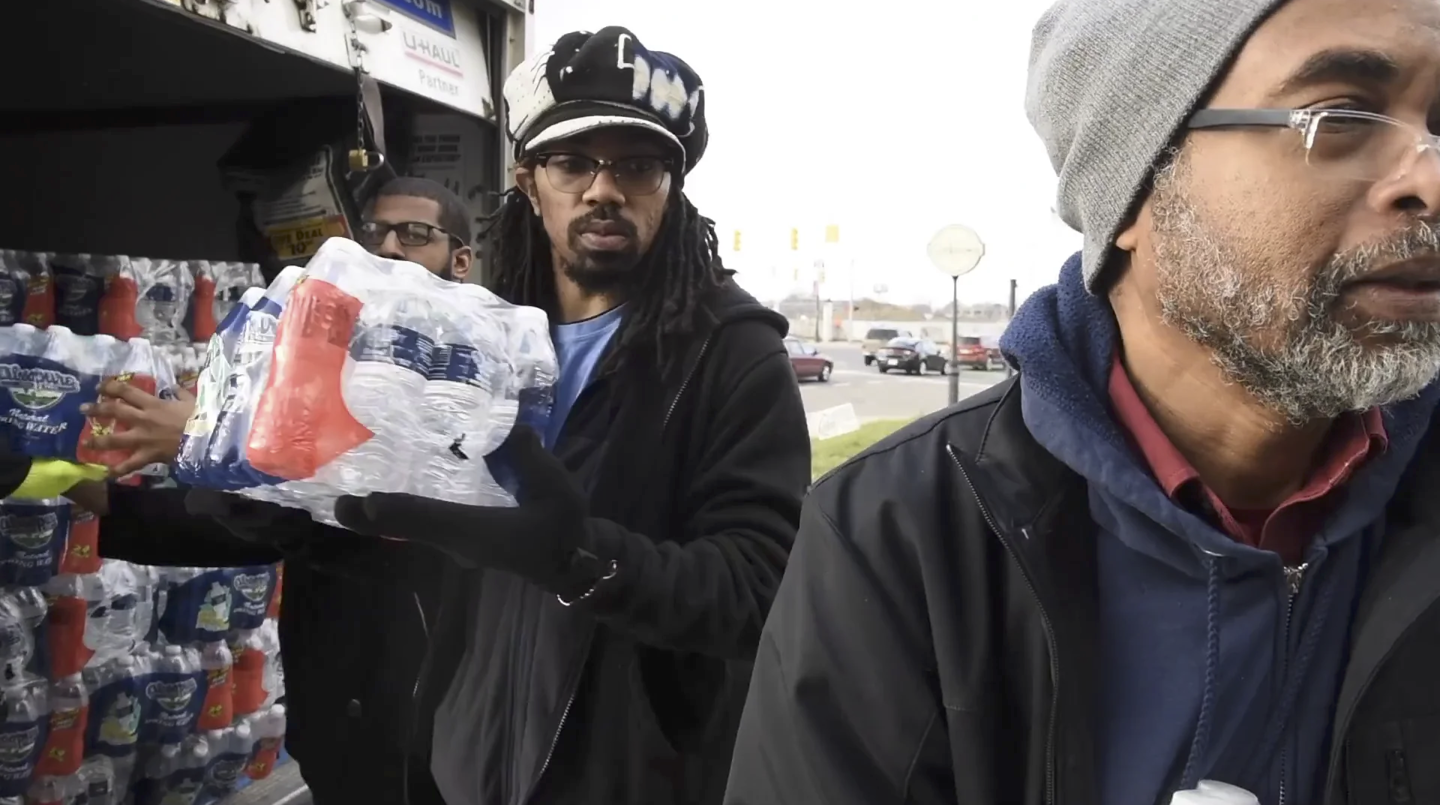 Dennis Black, B. Anthony Holley, and Kim Hunter unload water at the We the People of Detroit water station at St. Peter's Episcopal. Film still from Kate Levy, Detroit's Water Affordability Crisis, 2017.