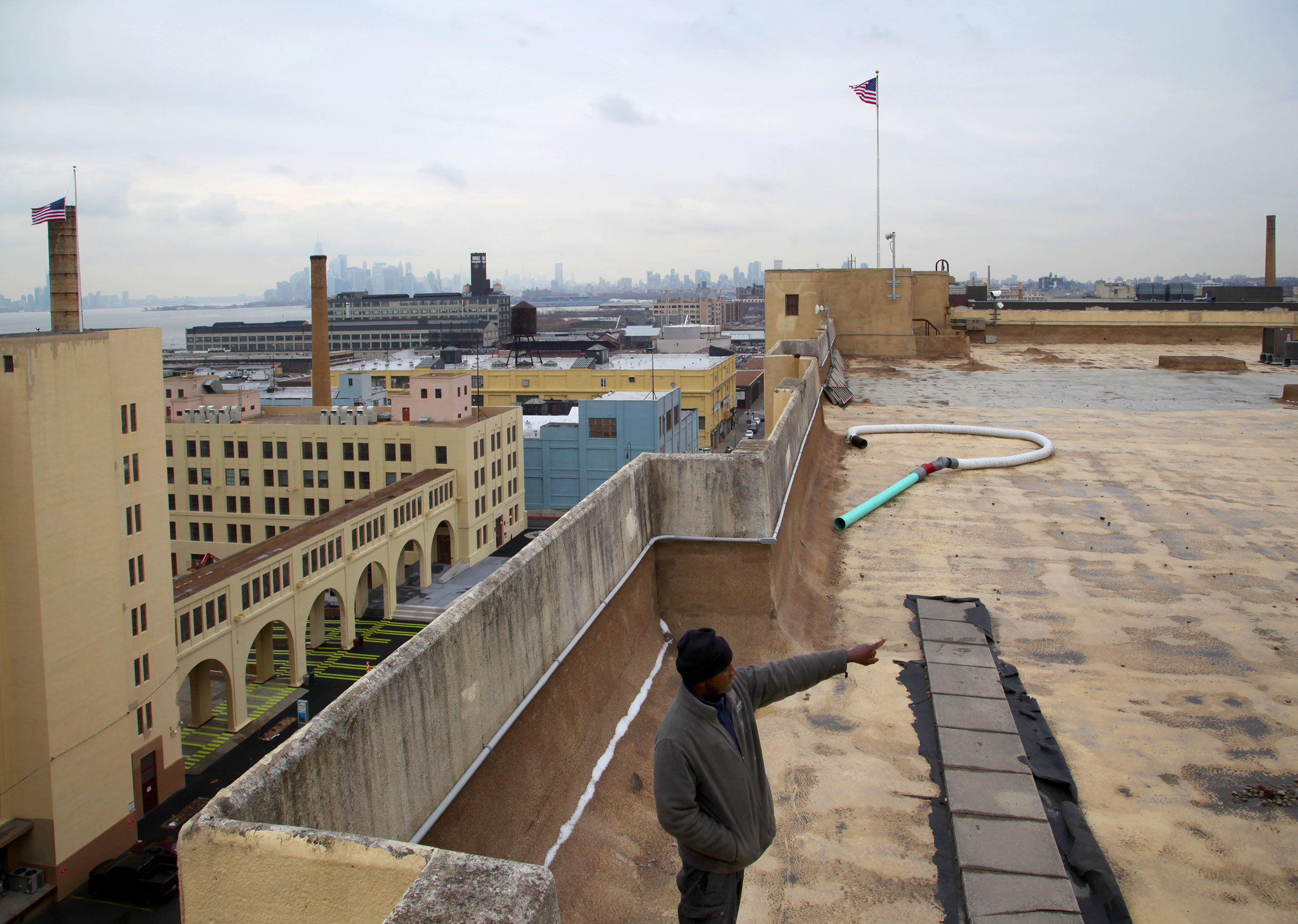Reginald Raspberry, mechanic at the Brooklyn Army Terminal, points to one of the parts of the roof of Building B where Sunset Park Solar will be installed. Photo by Amy Howden-Chapman