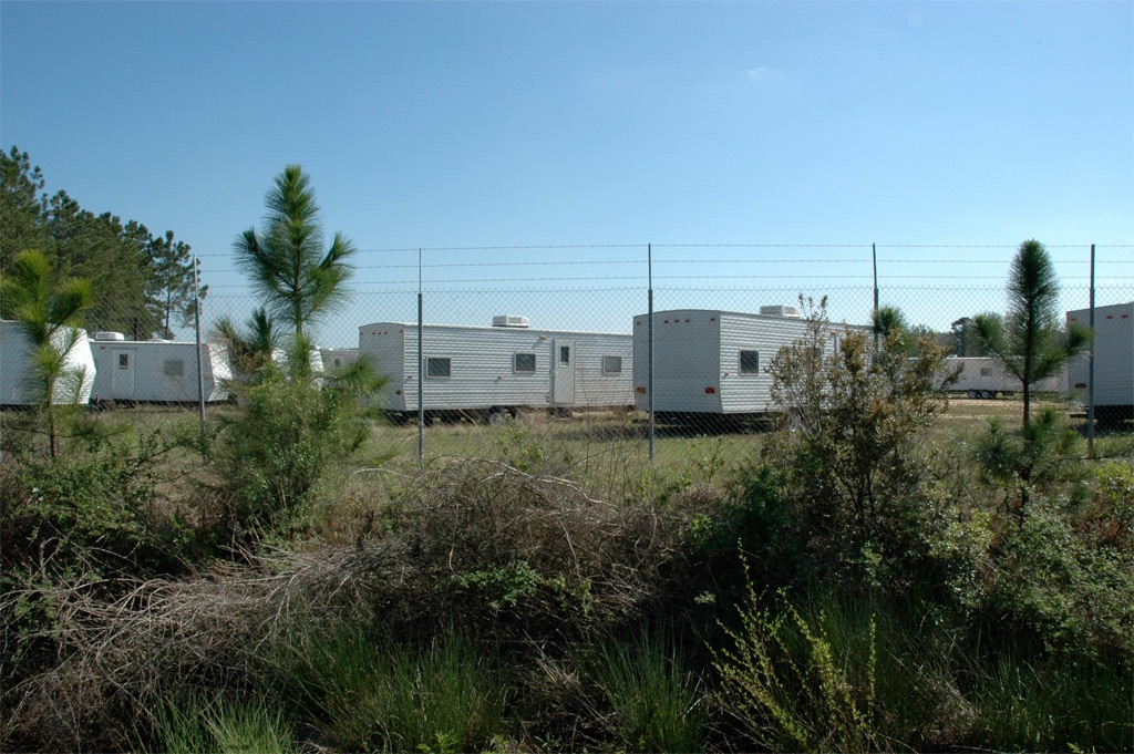 rows of mobile homes viewed through a fence