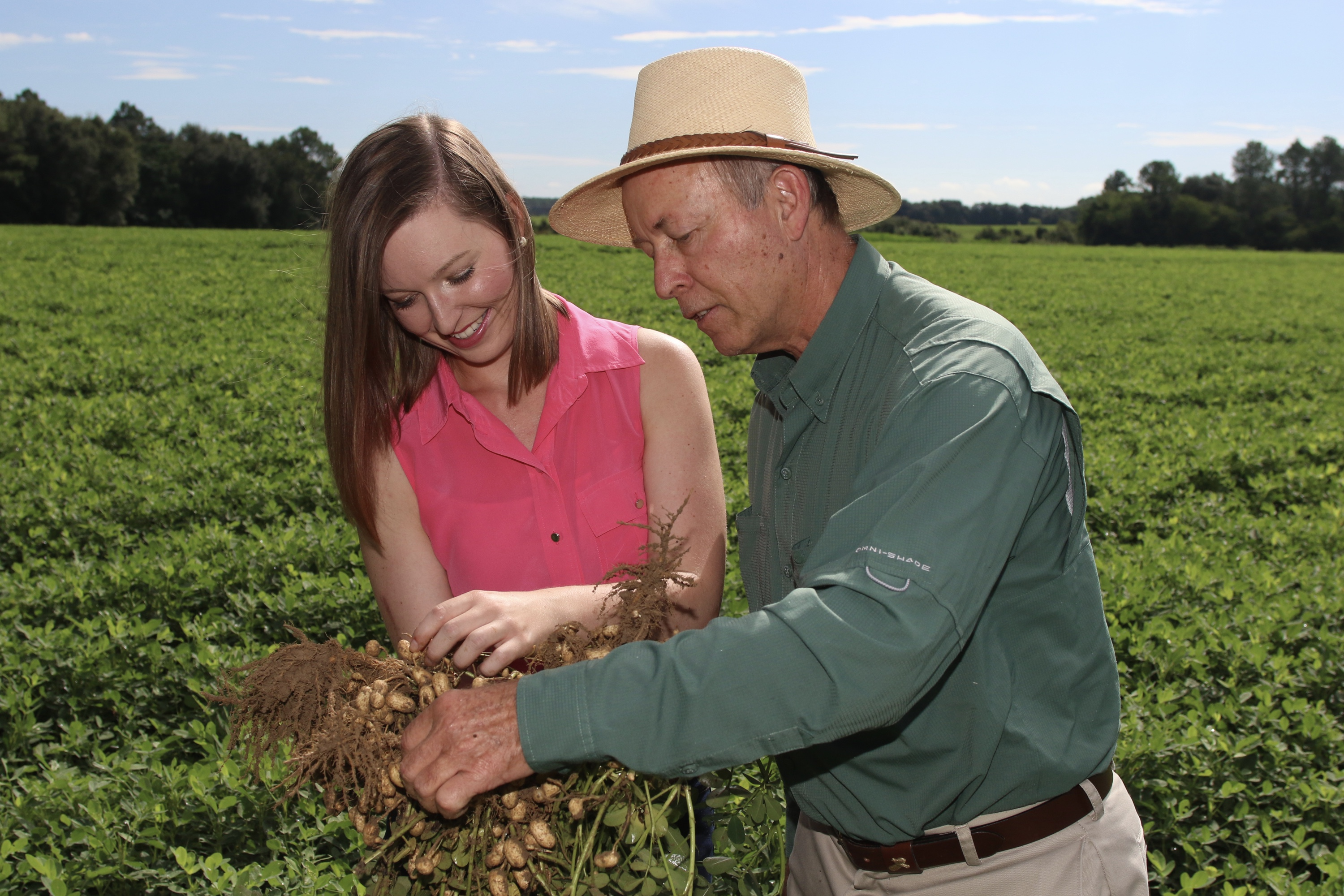 Casey Cox and her father, Glenn, on their family farm in South Georgia. Casey is smiling and touching a bunch of legumes her father is holding.