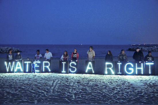 "People at a shore holding illuminated ""WATER IS A RIGHT"" signs"