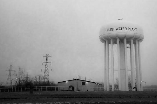 "A water tower with ""Flint Water Plant"" painted on it is shown against a grey sky."