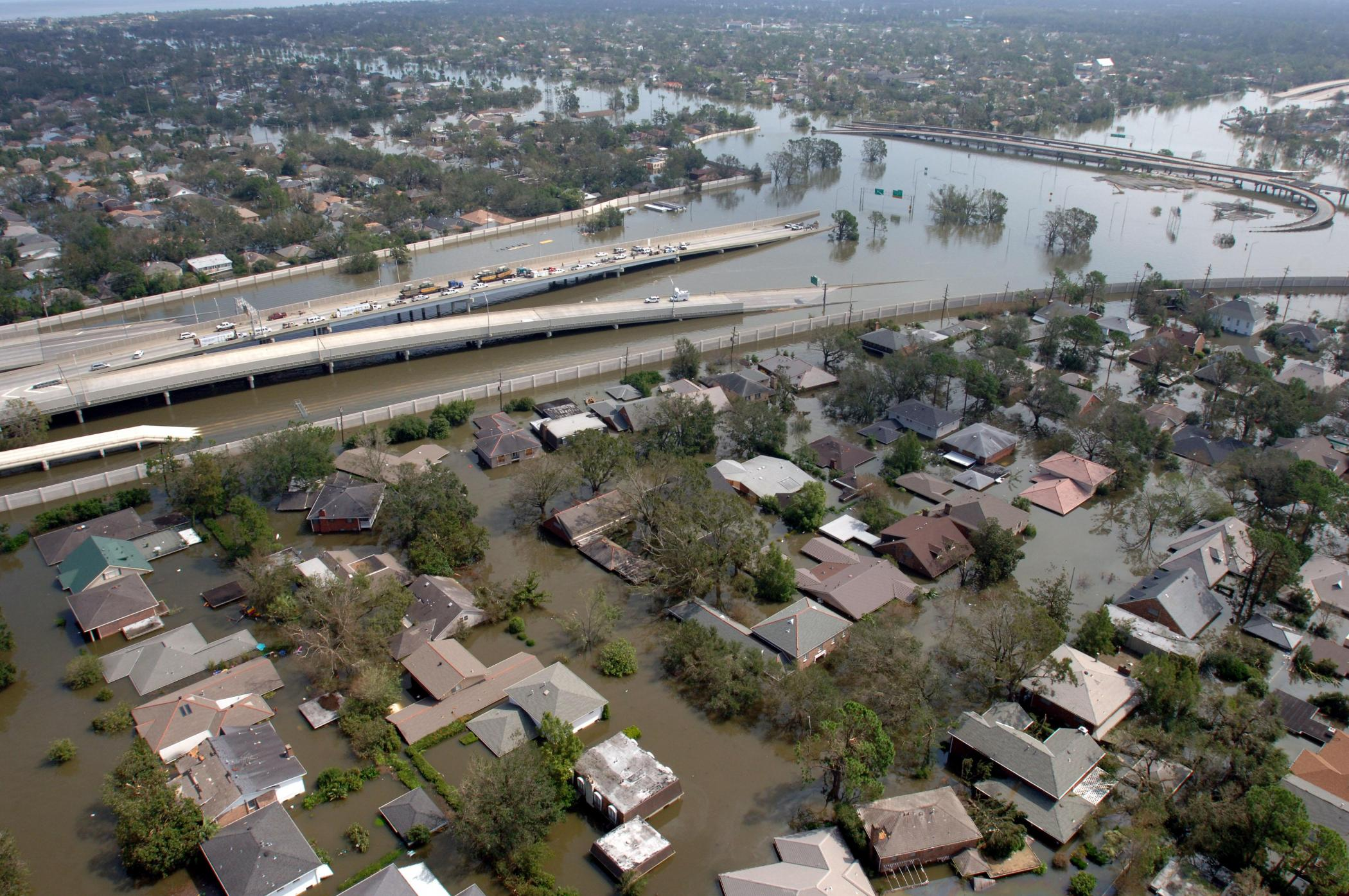 Flooded houses and highway shown from above, horizon in the distance