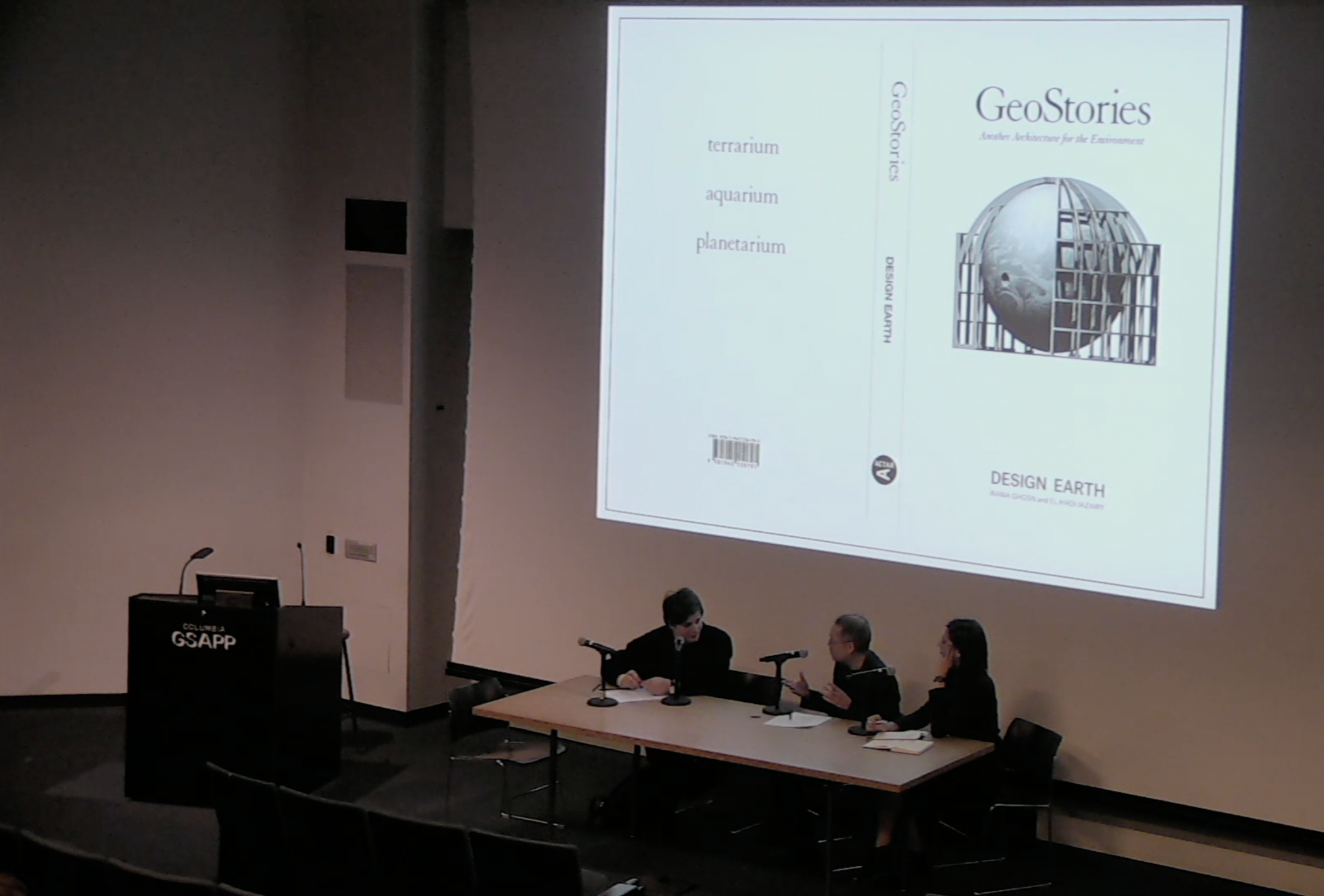 "Three people sit at a table with microphones in front of a large screen that shows the cover of a book titled ""GeoStories"""